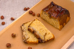 Homemade banana cake with hazelnuts on brown paper. Homemade banana cake with hazelnuts on a baking brown paper on a wooden board, close-up top view Stock Photos