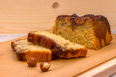 Homemade banana cake with hazelnuts on wooden board. Homemade banana cake with hazelnuts on a baking brown paper on a wooden board, close-up front view Stock Photography