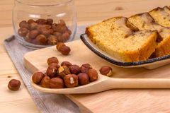 Homemade banana cake, wooden spoon with hazelnut. Slices of homemade banana cake, wooden spoon with hazelnuts, glass jar on a wooden board on a gray linen napkin Royalty Free Stock Images