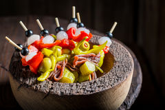 Homemade banderillas with peppers, olives and anchovies for spanish corrida. On wooden table Royalty Free Stock Photo