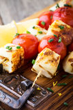 Homemade barbecue haloumi and cherry tomato kebabs. With lemon zest and spring onion, delicious summer meal Royalty Free Stock Images
