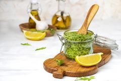 Homemade basil and arugula pesto in a glass jar stock images
