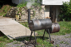Homemade BBQ Smoker. Homemade barbecue smoker in back yard with smoke royalty free stock image