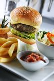 Homemade Beef Burger. With side dishes like fries,salad,and onion rings Royalty Free Stock Image