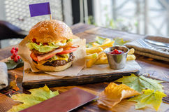 Homemade beef burger. Beef, cheese, tomatoes, onion, green salad, Tabasco sauce and French fries. On a wooden table royalty free stock photo