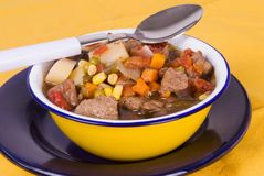 Homemade Beef Soup Served in a Yellow Tin Bowl Royalty Free Stock Photography