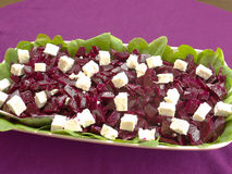 Homemade Beet Salad with Feta cheese. Beet salad with feta cheese in with green spinach leaves decoration on the side. Placed on a purple tablecloth Royalty Free Stock Photography