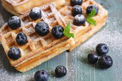Homemade Belgian waffles with blueberries are sprinkled with powdered sugar on a green wooden rustic background. Selective focus. stock images