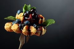 Homemade Belgian waffles with  chocolate syrup, blueberry and mint on a dark background royalty free stock image