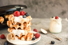 Homemade Belgian waffles with forest fruits,  blueberries, raspberries and  yogurt. Royalty Free Stock Photography