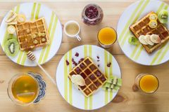Homemade Belgian waffles with jam, honey, pieces of banana, kiwi fruit, kumquat and cranberries on striped plates. stock images