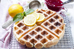 Homemade Belgian waffles with lemon and sugar powder. Selective focus Stock Images