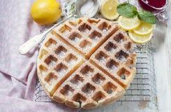 Homemade Belgian waffles with lemon and sugar powder. Selective focus Stock Photos
