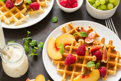 Homemade Belgian waffles with peach, raspberry, fig and honey Royalty Free Stock Photography