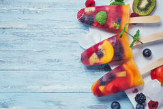Homemade berry and fruit ice pop on cyan background top view Royalty Free Stock Photography