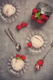 Homemade berry ice cream with fresh raspberries. Delicious berry ice cream on glass plate decorated with fresh raspberries on vintage gray background. Top view Stock Photos