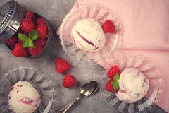 Homemade berry ice cream with fresh raspberries. Delicious berry ice cream on glass plate decorated with fresh raspberries on vintage gray background. Top view Stock Photo