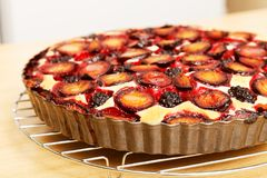Homemade berry pie with plums and blackberry. Closeup homemade berry pie with plums and blackberry on wooden table. Shallow focus stock images