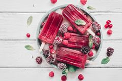 Homemade berry popsicles decorated berries and mint leaves on a white rustic wooden plank. Overhead view,flat lay stock photography