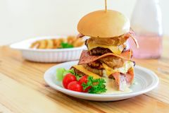 Homemade big burger. On wooden table Royalty Free Stock Photos