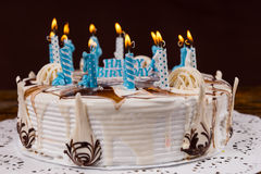 Homemade birthday cake with lots of blue burning candles Stock Photo