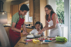 Homemade Birthday Cake!. Mother decorating a cake with her son and daughter in the kitchen of their home. They are covering the cake with icing and have sweets Stock Photography