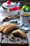 Homemade biscotti with dried cranberries and lime, with a cup of green tea kettle on the wooden table Royalty Free Stock Photo