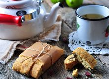 Homemade biscotti with dried cranberries and lime, with a cup of green tea kettle on the wooden table Royalty Free Stock Photos