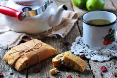 Homemade biscotti with dried cranberries and lime, with a cup of green tea kettle on the wooden table Royalty Free Stock Image