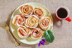 Homemade biscuits with apples in the form of rose on plate and c. Up of coffee on sackcloth. Top view Royalty Free Stock Photos