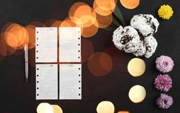 Homemade biscuits, sheets for notes, a silver pen and flowers on stone black table. Top view with bokeh lights effects.  royalty free stock images