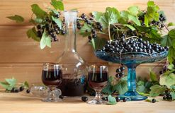 Homemade black currant liqueur and fresh berries . Homemade black currant liqueur and fresh berries on a branch , wooden background stock images