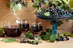 Homemade black currant liqueur and fresh berries . Homemade black currant liqueur and fresh berries on a branch , wooden background royalty free stock photography