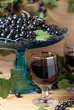 Homemade black currant liqueur and fresh berries . Homemade black currant liqueur and fresh berries on a branch , wooden background royalty free stock images