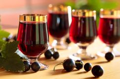 Homemade black currant liqueur and fresh berries. Wooden background stock images