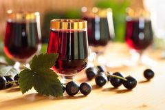 Homemade black currant liqueur and fresh berries. Homemade black currant liqueur and fresh berries, wooden background stock photography