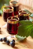 Homemade black currant liqueur and fresh berries. Homemade black currant liqueur and fresh berries, wooden background royalty free stock image