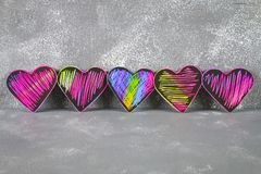 Homemade Black violet pink hearts on a gray concrete background. The concept of Valentine's Day. A symbol of love. Homemade Black violet pink hearts on a gray Stock Images