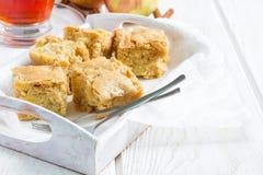 Homemade blondie brownies apple cake, square slices, copy space. Homemade blondie (blonde) brownies apple cake, square slices in wooden tray, horizontal, copy Royalty Free Stock Image