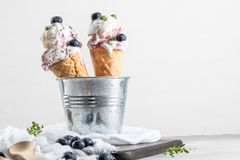 Homemade blueberries ice cream in waffle cones and fresh blueberries. stock photo