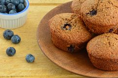 Homemade blueberry bran muffins. On rustic wooden plate with blueberries in horizontal format  and shot in natural light Stock Photo