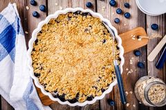 Homemade blueberry crumble with oatmeal. On wooden table stock photo