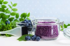 Homemade blueberry face and body sugar scrub/bath salts/foot soak in a glass jar. DIY cosmetics for natural skin care. Copy space. Homemade blueberry face and royalty free stock image