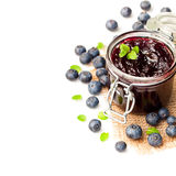 Homemade  blueberry jam in a jar and fresh blueberries isolated Stock Photography