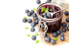 Homemade   blueberry jam in a jar and fresh blueberries isolated Royalty Free Stock Photography