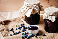 Homemade blueberry jam in a jar and fresh blueberries on  table. Stock Images
