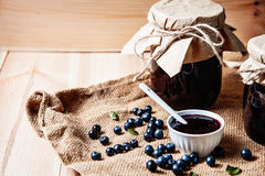 Homemade blueberry jam in a jar and fresh blueberries on table. Stock Image