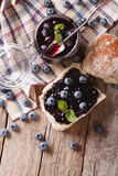 Homemade blueberry jam and sweet bun close-up. Vertical top view Stock Image