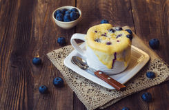 Homemade blueberry muffin mug cake. Delicious homemade blueberry muffin mug cake with fresh berries on rustic wooden background. Cooked in a cup in the microwave Stock Photos