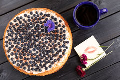 Homemade blueberry pie with a cup of coffee and flowers. Lip pri Stock Images